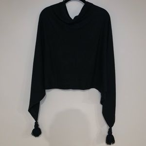 Black sweater poncho with tassels.